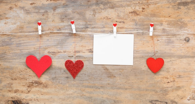 Red hearts with paper hanging on rope Free Photo