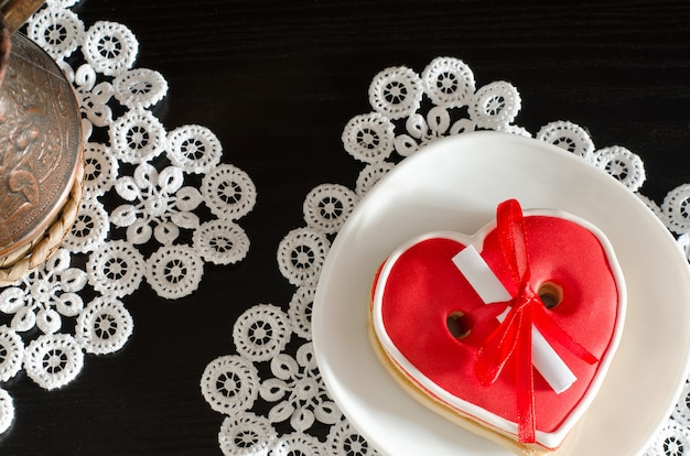 Red heartshaped gingerbread with a message on a white plate Premium Photo