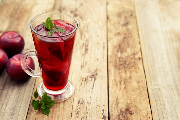 Red herbal and fruit tea in glass cup and tea with plums. Premium Photo