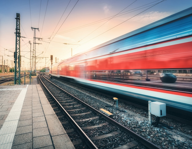 Red high speed train in motion on the railway station Premium Photo