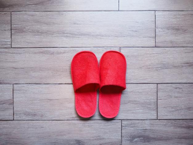 木製の床タイルに赤い家の布使い捨てスリッパ Premium写真