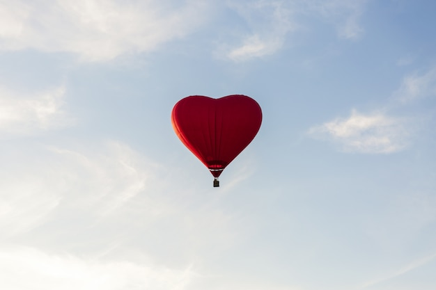 Red hot air balloon in the shape of a heart fly in sky. love, honeymoon and romantic travel concept Premium Photo