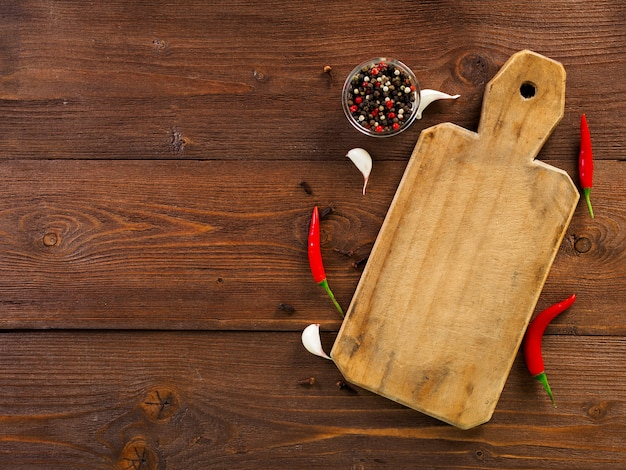 Red hot chili pepper pods and peas, cutting board, garlic clove Premium Photo