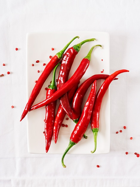 Red hot chili peppers in plate on white table. Premium Photo