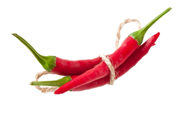 Red hot chili peppers tied with rope on white Free Photo