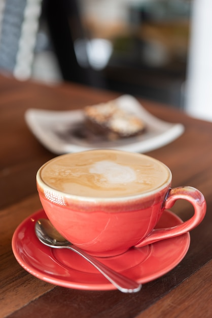 Red hot coffee cup and bakery on wood table in restaurant Premium Photo