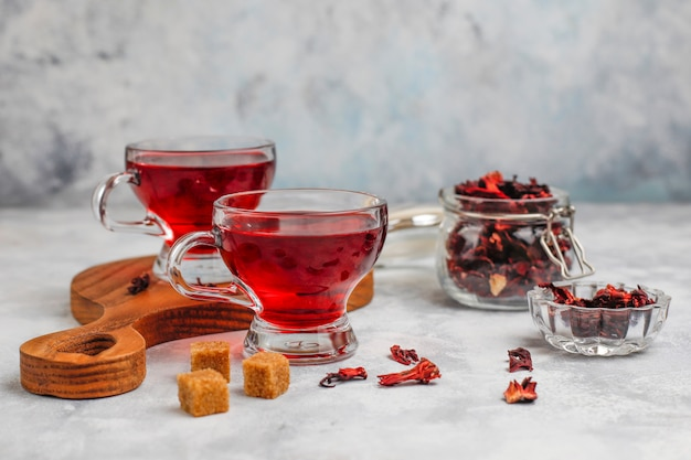 Red hot hibiscus tea in a glass mug on concrete  with dry hibiscus petals Free Photo