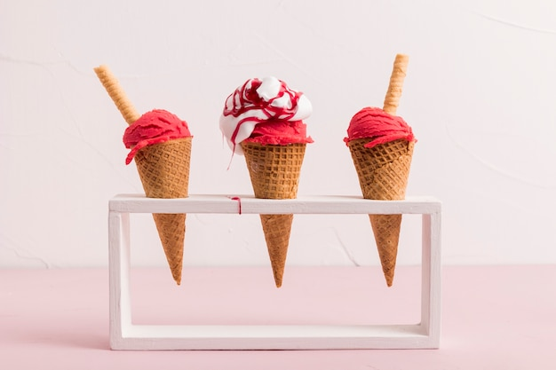 Red ice cream scoop in cones with syrup and waffle straw on stand Free Photo