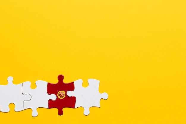 Red jigsaw puzzle piece with dartboard symbol arranged with white piece on yellow background Free Photo