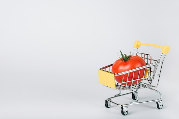 Red juicy tomato in shopping cart on white backdrop Free Photo