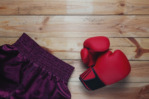 Red leather mitt glove and boxing pants on wooden table Free Photo