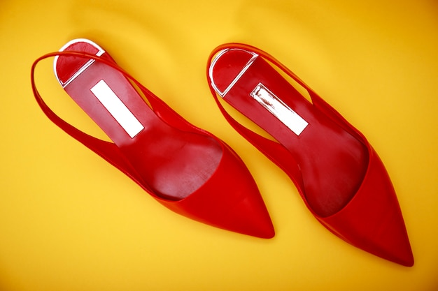 Red leather woman shoes isolated on yellow Premium Photo