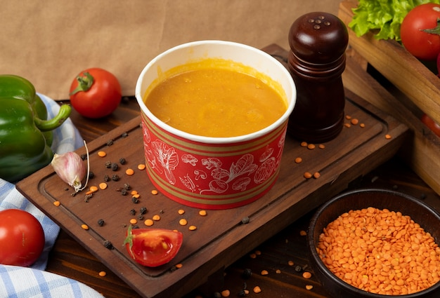 Red lentil soup in disposable cup bowl served with green vegetables. Free Photo