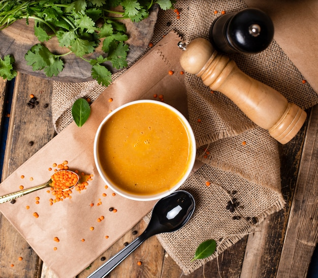 Red lentil soup in disposable cup bowl served with green vegetables Free Photo
