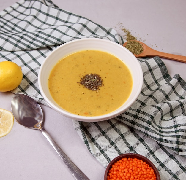 Red lentil soup with herbs in the white bowl. Free Photo