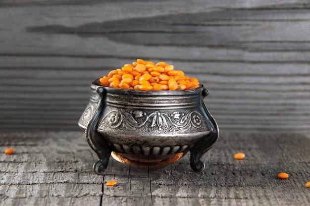 Red lentils in vintage silver jar on old wooden background. Premium Photo