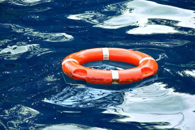 Red lifebuoy in blue water. Free Photo