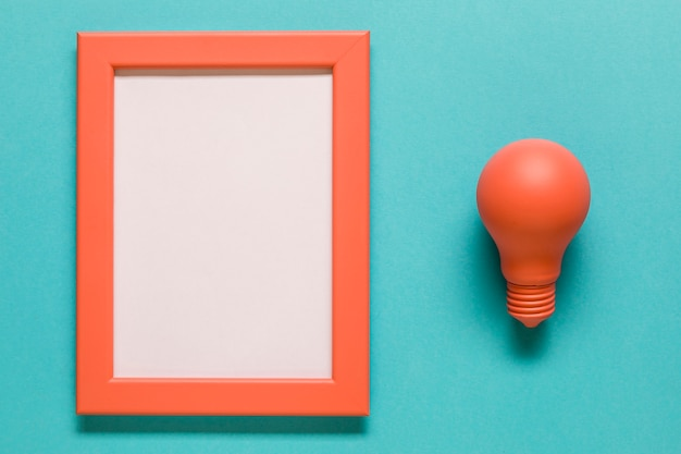 Red light bulb and empty frame on blue background Free Photo