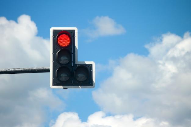 青い空を背景に赤信号。 Premium写真