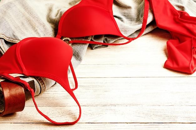 빨간 란제리와 청바지가 바닥에 흩어져 있습니다. 지저분한 옷 프리미엄 사진