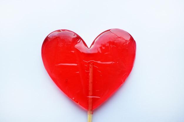 赤いロリポップ。赤いハート。キャンディー。愛と甘いコンセプト。バレンタインデー。 Premium写真