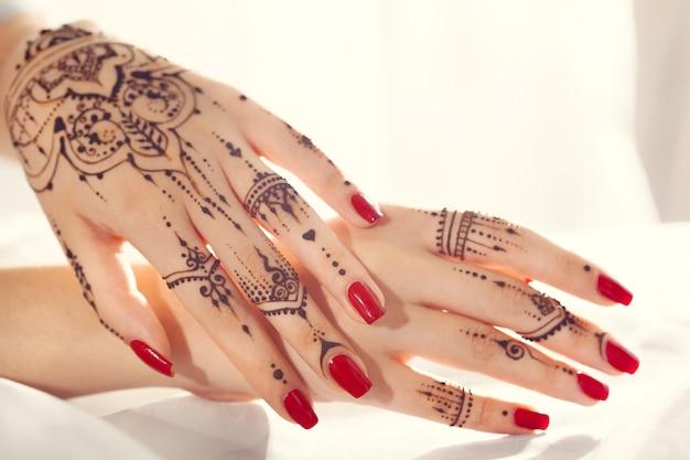 Red manicured hands with mehndi Premium Photo