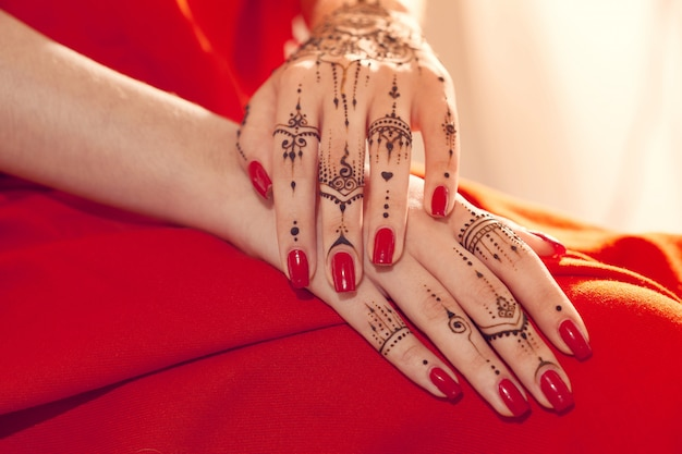 Red manicured hands with mehndi Premium Photo
