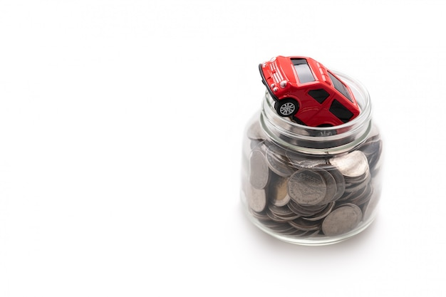 A red model car on many coins in a glass jar isolated on white background and copy space, saving and investment concept Premium Photo