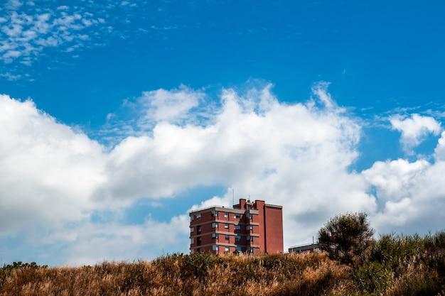 Edificio residenziale a più piani rosso e un cielo nuvoloso Foto Gratuite