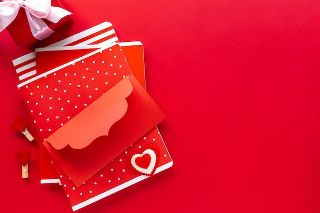 Красные тетради, конверт, подарок в коробке с смычком на красной таблице с космосом экземпляра. вид сверху Premium Фотографии