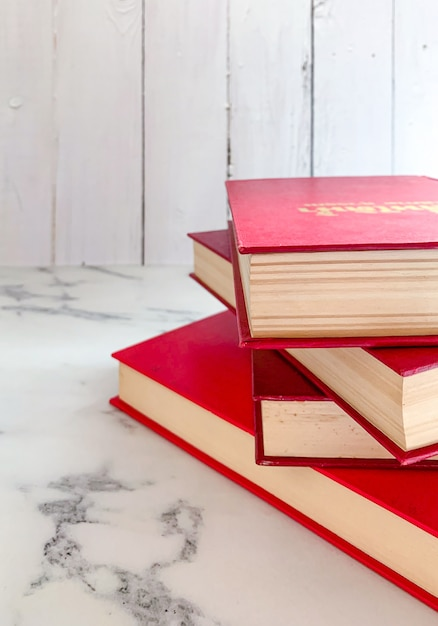 Red novels stack on marble floor Premium Photo