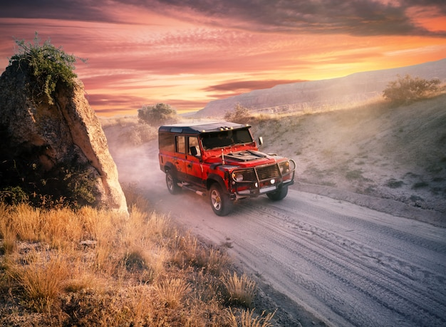 Red off-road car on a dusty road Premium Photo