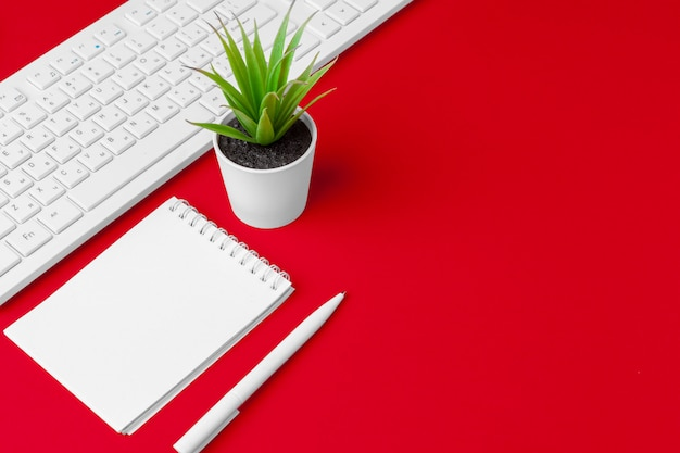 Red office desk table with blank notebook, keyboard and supplies. top view with copy space. flat lay. Premium Photo
