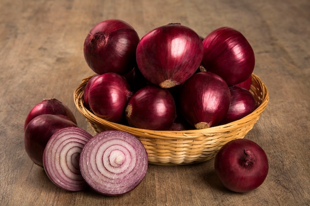 Red onions in a basket and a cut red onion over a table. onions. Premium Photo