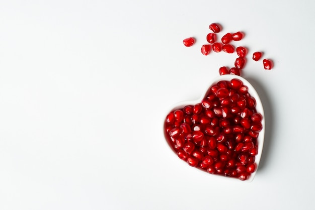 Red organic tasty pomegranate seeds with love Premium Photo