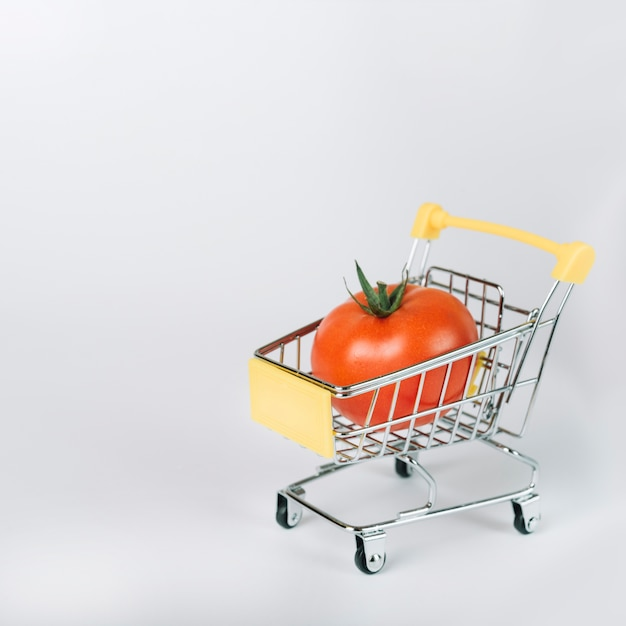 Red organic tomato in shopping cart on white background Free Photo