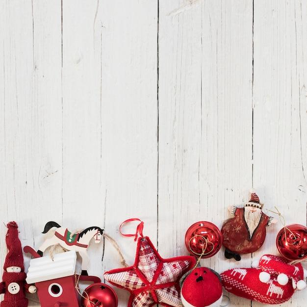 白い木製の背景の上のクリスマスツリーの赤い飾り 無料写真