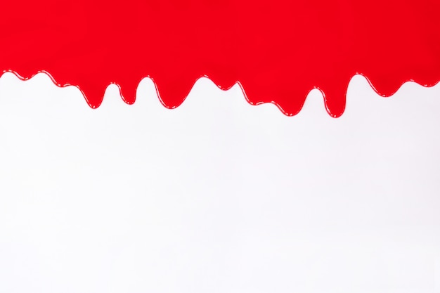 Red paint dripping on a white. Premium Photo