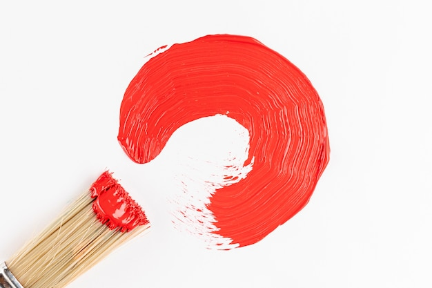 Red paint semicircle and brush Free Photo