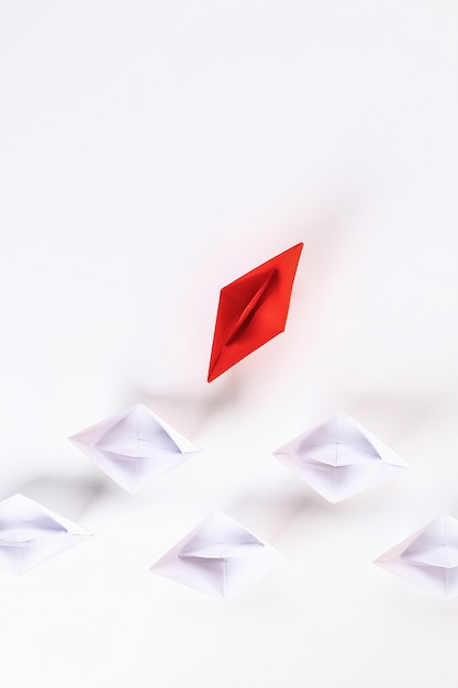 Red paper boat among other white. Premium Photo