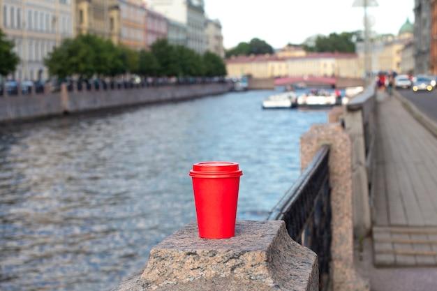 川の堤防の手すりにコーヒーの赤い紙コップ Premium写真