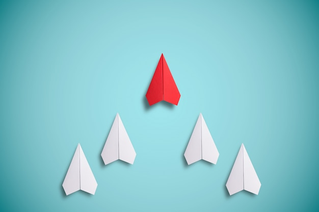 Red paper flying in front of white paper. leadership concept. Premium Photo