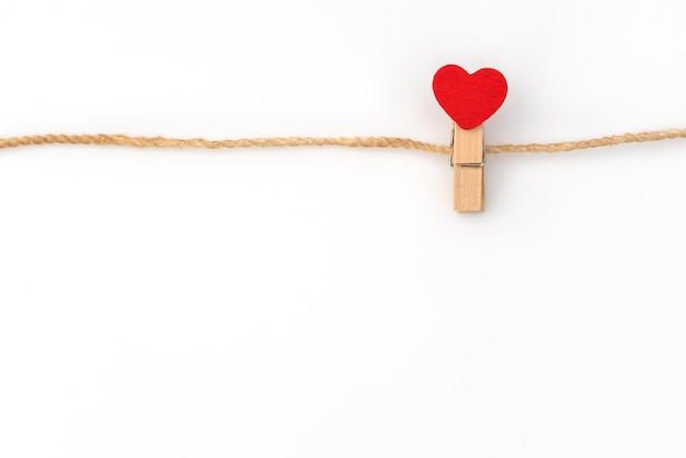Red paper heart hanging on white background . Free Photo
