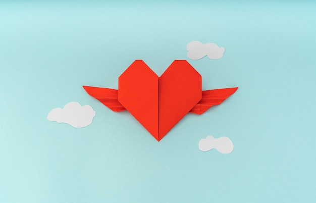 Red paper origami heart with wings and cloud on blue background Free Photo