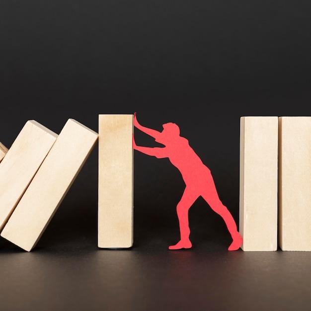 Persona di carta rossa che lotta mentre tiene i pezzi di legno Foto Gratuite