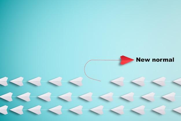 Красный бумажный самолет из линии с белой бумагой, чтобы изменить нарушить и найти новый нормальный путь на синем фоне. Premium Фотографии