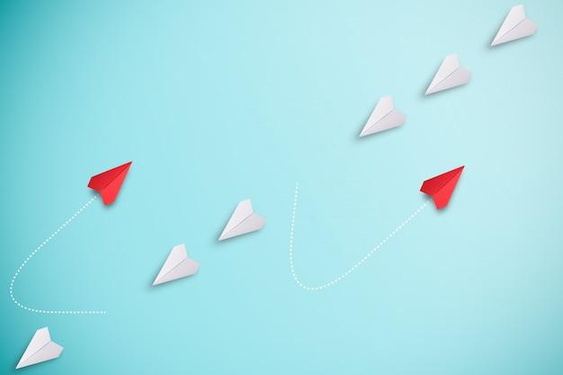 Красная бумажная плоскость выходит за линию с белой бумагой, чтобы изменить нарушить и найти новый нормальный путь на синей стене. лифт и бизнес-творчество новая идея для открытия инновационных технологий. Premium Фотографии