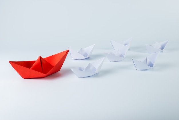 Red paper ship leading among white Premium Photo