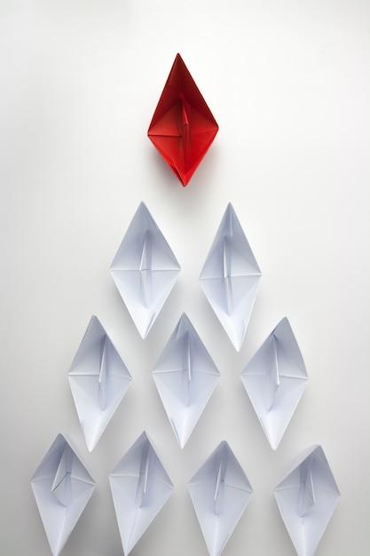 Red paper ship leading white ones Premium Photo