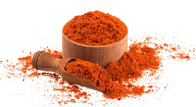 Red paprika powder in wooden bowl and scoop isolated on white Premium Photo